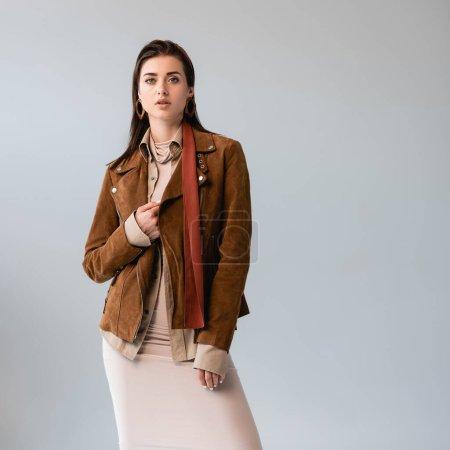 Photo pour Attrayant, fille à la mode touchant veste en daim tout en regardant la caméra isolée sur gris - image libre de droit