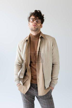 Photo pour Confiant, élégant homme regardant caméra tout en tenant les mains dans des poches isolées sur gris - image libre de droit