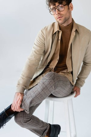 Photo for Stylish, confident man looking at camera while sitting on stool and touching leg isolated on grey - Royalty Free Image
