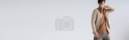 Photo pour En-tête de site Web de l'homme élégant toucher le cou tout en posant isolé sur gris - image libre de droit