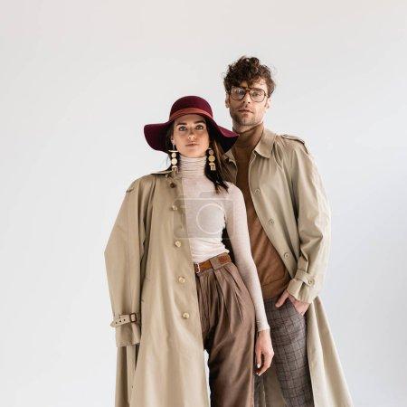 Photo pour Femme élégante en chapeau et homme à la mode en lunettes posant en vêtements d'automne isolé sur gris - image libre de droit
