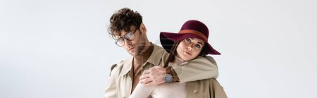 panoramic shot of handsome man hugging stylish woman in hat while looking at camera isolated on white