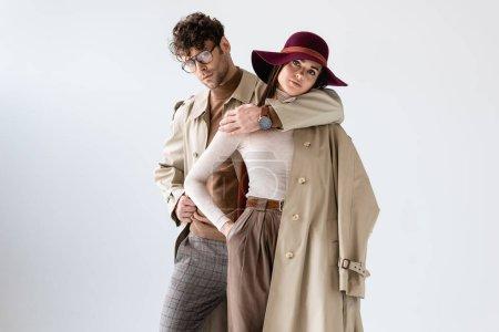 Photo pour Élégant homme étreignant femme à la mode tout en posant en tenue d'automne isolé sur gris - image libre de droit
