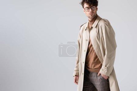 gutaussehender, modischer Mann, der die Hand in der Tasche hält und isoliert auf grau blickt