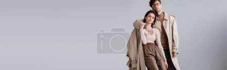 panoramic shot of trendy man embracing fashionable woman while looking at camera isolated on grey
