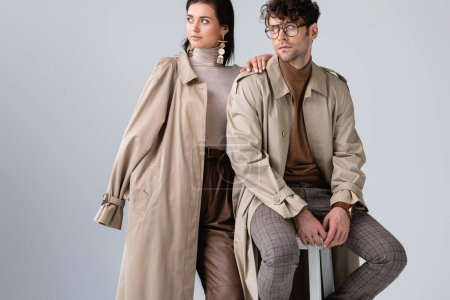 trendy woman looking away while touching shoulder of stylish man sitting on stool isolated on grey