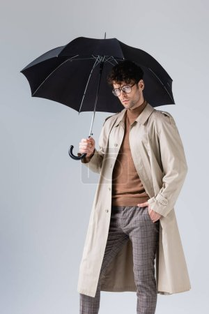 Photo for Confident, trendy man standing under umbrella with hand in pocket on grey - Royalty Free Image