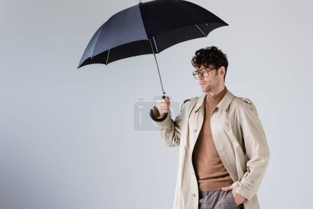 stylish man with hand in pocket holding umbrella and looking away isolated on grey