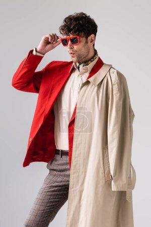 selbstbewusster, stylischer Mann mit Sonnenbrille, während er isoliert von grau wegschaut
