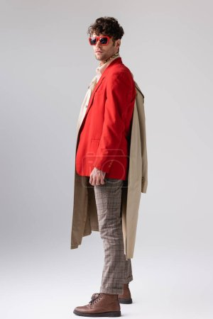 full length view of stylish man in red blazer holding trench coat and looking at camera on grey
