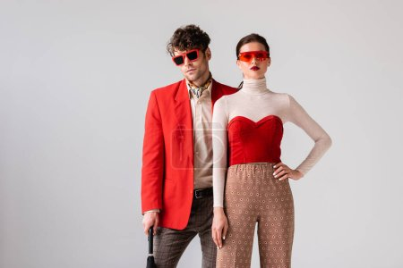 fashionable couple in sunglasses looking at camera isolated on grey