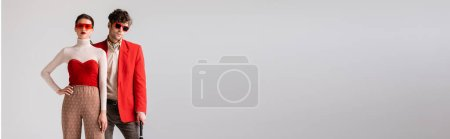 website header of fashionable young couple in autumn clothes posing isolated on grey