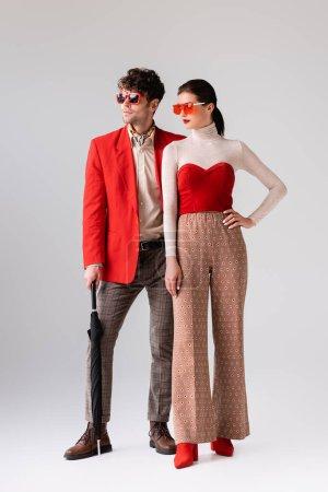 Ganzkörperansicht eines stilvollen Paares mit Sonnenbrille, das auf grau wegschaut