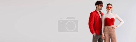 panoramische Ernte von stilvoller Frau mit Hand an der Hüfte neben trendigem Mann in rotem Blazer isoliert auf grau