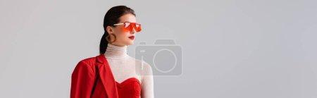Panoramaaufnahme eines eleganten Mädchens mit roter Sonnenbrille, das isoliert von grau wegschaut
