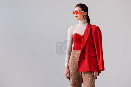 schönes, stylisches Mädchen mit Sonnenbrille, das wegschaut, während es isoliert auf grau posiert