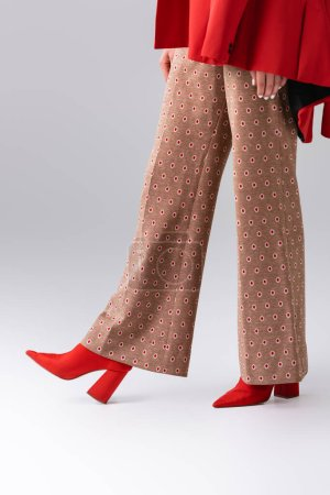 cropped view of trendy girl in beige trousers and red boots on grey