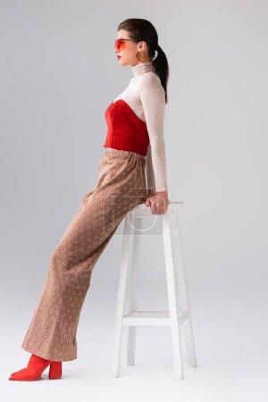 Foto de Vista lateral de chica de moda en pantalones beige y corsé rojo en cuello alto apoyado en taburete en gris - Imagen libre de derechos