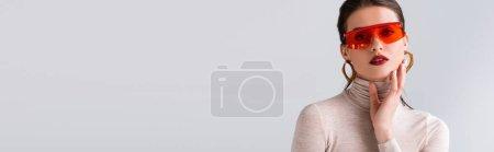 Photo pour Image horizontale de la fille élégante dans des lunettes de soleil rouges regardant la caméra et toucher le visage isolé sur le gris - image libre de droit