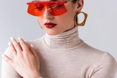 Photo pour Élégante fille en lunettes de soleil rouges touchant épaule tout en posant isolé sur gris - image libre de droit