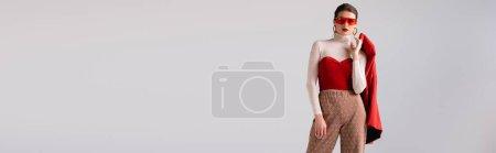 horizontales Bild eines stilvollen Mädchens mit Sonnenbrille, rotem Blazer und Blick in die Kamera isoliert auf grau