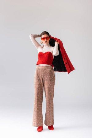 Ganzkörperansicht des eleganten Mädchens mit Sonnenbrille und rotem Blazer auf grau