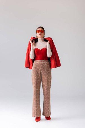 Ganzkörperansicht attraktiver, stylischer Mädchen mit rotem Blazer, während sie in die Kamera auf grau schaut