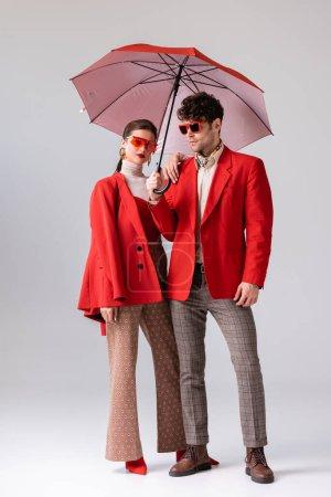 Ganzkörperansicht des trendigen Paares in roten Blazern und Sonnenbrille posiert mit Sonnenschirm auf grau