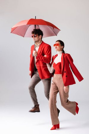 full length view of trendy couple in red blazers and sunglasses running with umbrella on grey