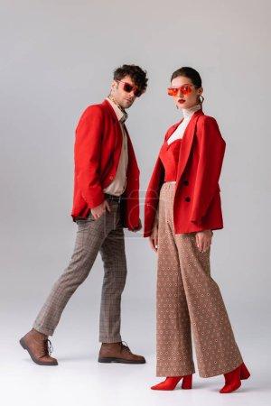 Ganzkörperansicht eines modischen Paares in roten Blazern und Sonnenbrille, das auf grau in die Kamera blickt