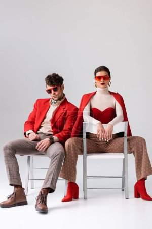 stylish couple in sunglasses sitting on chairs and looking at camera on grey