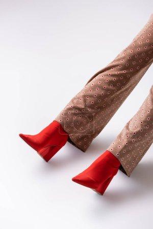 Photo pour Vue recadrée des jambes féminines en pantalon marron et bottes rouges sur fond gris - image libre de droit