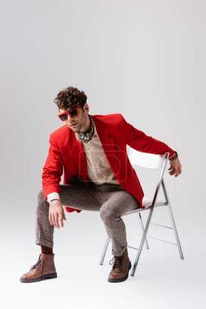 Photo for Stylish man in red blazer leaning forward and posing while sitting on chair on grey - Royalty Free Image