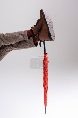 Photo pour Vue partielle des jambes de l'homme appuyées sur le parapluie rouge sur le gris - image libre de droit