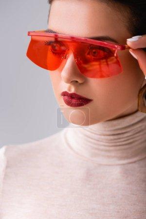Photo pour Portrait de jolie fille en lunettes de soleil rouges regardant loin et cadres touchants isolés sur gris - image libre de droit