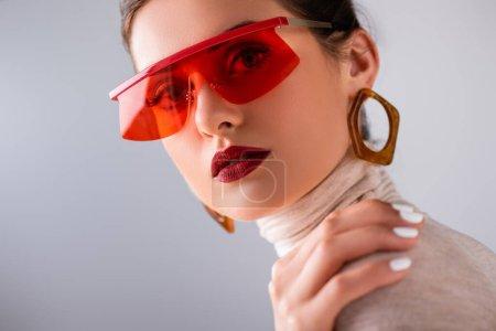 Photo pour Jolie fille en lunettes de soleil rouges touchant l'épaule et regardant la caméra isolée sur gris - image libre de droit