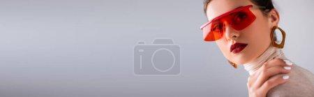 Photo pour Vue panoramique de belle femme en lunettes de soleil rouges touchant les épaules avec la main et regardant la caméra isolée sur gris - image libre de droit