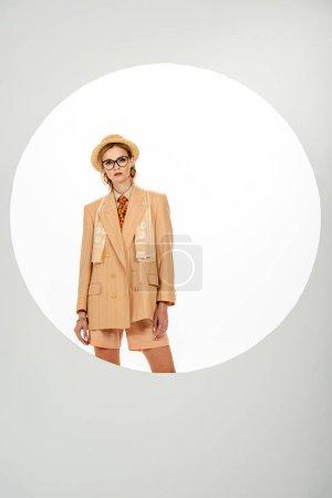 Schöne stilvolle Frau schaut in die Kamera in der Nähe Kreis auf weißem Hintergrund