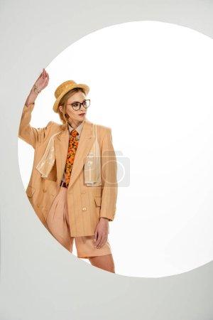 Photo pour Fille élégante en chapeau de paille et lunettes debout près du cercle sur fond blanc - image libre de droit