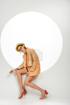 Photo pour Jeune femme élégante posant dans un trou rond sur fond blanc - image libre de droit