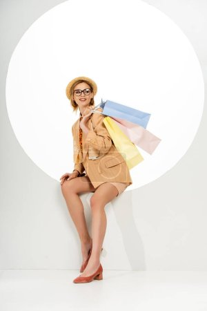 Attractive girl in straw hat and beige blazer smiling away while holding shopping bags in circle on white background