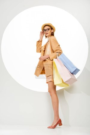 Photo pour Vue latérale de la femme élégante avec des sacs à provisions tenant des lunettes et souriant près du cercle sur fond blanc - image libre de droit