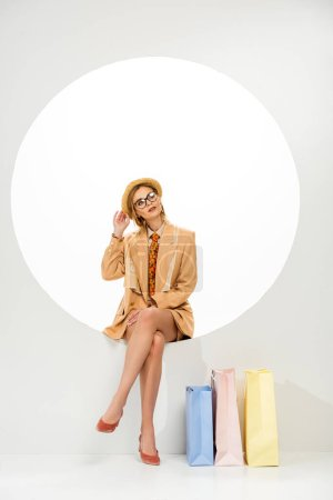 Photo pour Fille à la mode touchant chapeau de paille tout en étant assis en cercle près de sacs à provisions sur fond blanc - image libre de droit