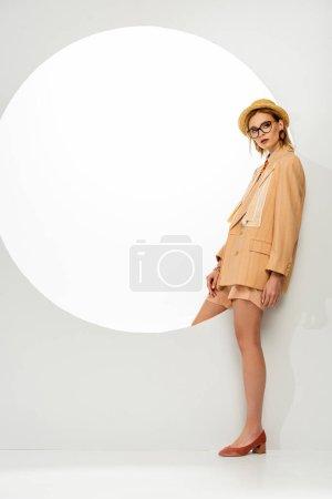 Photo pour Femme à la mode en veste et chapeau de paille regardant la caméra près du cercle sur fond blanc - image libre de droit