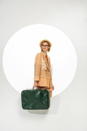 Beautiful stylish girl holding green travel bag near circle on white background