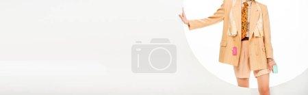 Photo pour Récolte panoramique de fille dans les vêtements avec des étiquettes de prix debout près du trou rond sur fond blanc - image libre de droit
