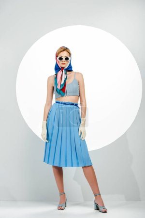 Photo pour Femme élégante en lunettes de soleil et jupe bleue debout près du cercle sur fond blanc - image libre de droit