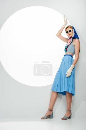 Photo pour Femme élégante en lunettes de soleil et foulard posant près du trou rond sur fond blanc - image libre de droit