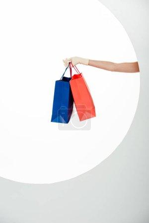 Photo pour Vue recadrée de la femme en gant tenant des sacs à provisions bleus et rouges sur fond blanc - image libre de droit