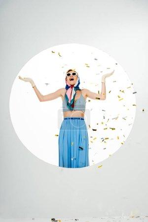 Photo pour Choqué femme élégante debout sous confettis tombant près du cercle sur fond blanc - image libre de droit
